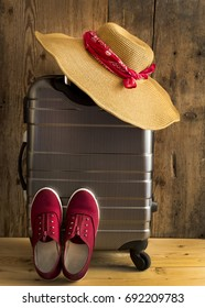 Holiday suitcase and straw hat with red foulard. Travel concept