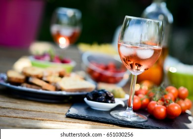 holiday summer brunch party table outdoor in a house backyard with appetizer, glass of rose wine, fresh drink and organic vegetables