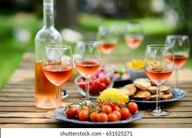 holiday summer brunch party table outdoor in a house backyard with appetizer, glass of rosé wine, fresh drink and organic vegetables
