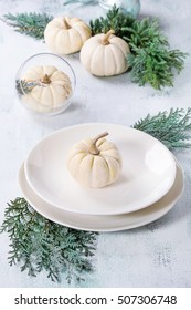 Holiday table setting decoration with white decorative pumpkins, thuja branches and dinner plates over white wooden background.