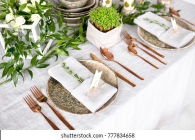 Holiday table setting with Linen napkins and rose gold cutlery. Close up