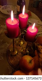 Holiday table with three red candles in vintage copper candelabras. Candlelight flames of cylindrical wax candles. Burning candlesticks on blurred background of table setting with fruits and dishes.