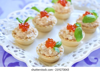 Holiday tartlets with seafood salad, red caviar and basil