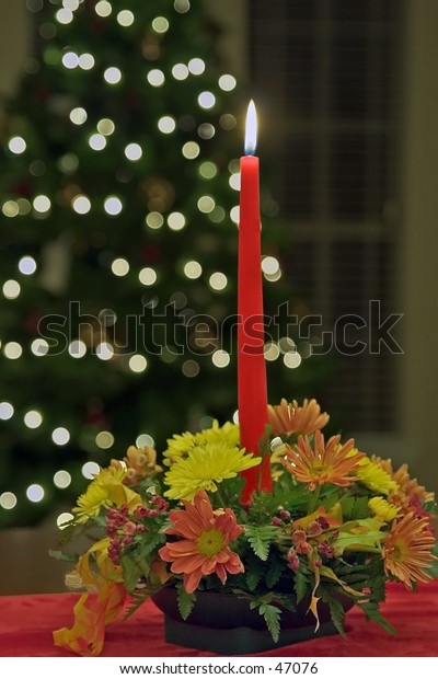 Holiday Themed - Candle sitting on table w/ Christmas Tree in background.