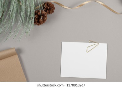 Holiday themed pine cones and gold ribbon on gray background with white notecard