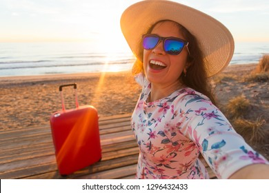 Holiday, travel and tourism concept - Beautiful young woman with red suitcase taking selfies on the beach