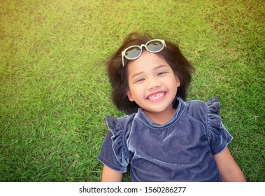 Holiday vacation of children concept. Little cute girl laying relax on green grass meadow nature field in nice environment of fresh spring or summer. Portrait of young girl kid in park.