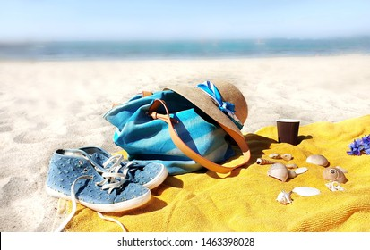 Holiday vacation on tropical island sun blue sky blue handbag yellow towel cup of coffee seashell and sneakers with red dress on white sand seascape background girl and women summer clothes copy space