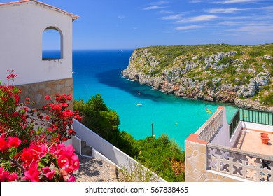 Holiday villa overlooking Cala Porter bay with turquoise sea water, Menorca island, Spain