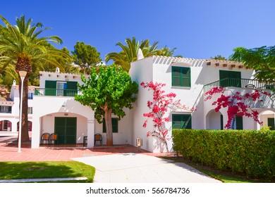 Holiday villas and palm trees in Cala Galdana village, Menorca island, Spain