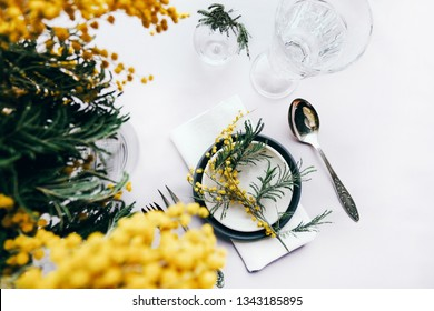 Holiday wedding table setting with mimosa flowers and linen napkin top view. Close up holiday table setting background for wallpaper, design, lettering, cards, blogs.