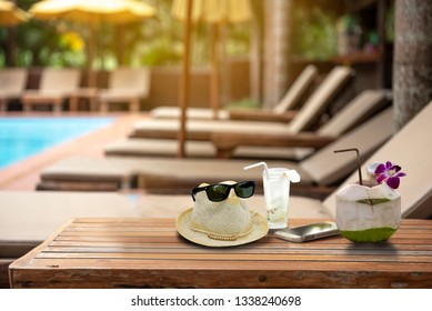 Holiday week end , relax concept,coconut, hat with sunglasses and smarthphone on wooden table near  bench pool villa beach side - Image