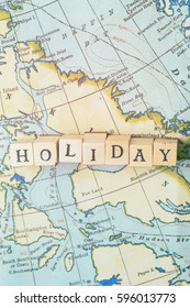 Holiday word made from wooden letter blocks on a vintage map. Travel, holiday concept