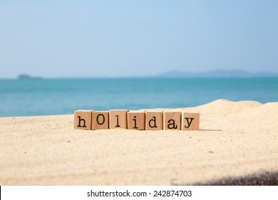 Holiday word on wood rubber stamps stack on the sand beach for vacation and summer season concept, beautiful sea view during daytime on a sunny day with blue sky on background