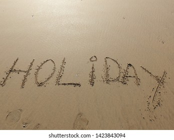""""""" holiday """" word is written  by hand  on the beach sand ."""