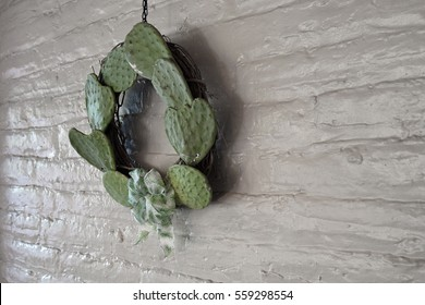 Holiday wreath made out of cactus leaves hanging on a white-painted brick wall