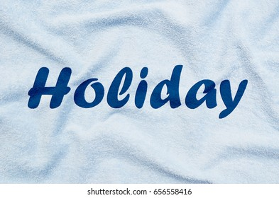 HOLIDAY written on a towel
