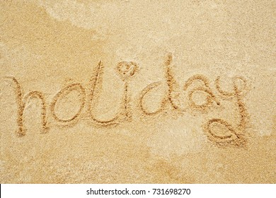 """Holiday"" written in the sand on the beach blue waves in the background"