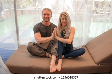 holiday yoga retreat portrait of young happy and beautiful hipster couple sitting in lotus position together enjoying zen lifestyle smiling cheerful and relaxed in wellness balance and harmony