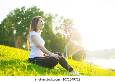 Holiday young woman doing yoga pose meditation in the public park Sport Healthy concept.