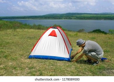 A holidaymaker camper is preparing tent on the meadow field near lakeside. Alone camping near lakeside. Camping lifestyle vacations concept.