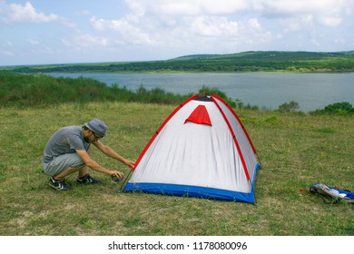 A holidaymaker camper is setting up tent on the meadow field near lakeside. Alone camping near lakeside. Camping lifestyle vacations concept.