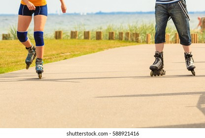 Holidays, active people and friendship concept. Young fit couple on roller skates riding outdoors on sea shore, woman and man rollerblading together on the promenade