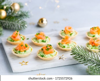 Holidays appetizer canapes with salmon avocado cream cheese on a light background with Christmas decorations. Festive table recipe ideas for New Year's and Christmas holidays.