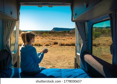 Holidays in Australia. Woman having a coffee at the back side of a caravan. Van life, coffee cup on her hands. Morning time. Motorhome without logos parked in front of Kings Canyon, NT Australia
