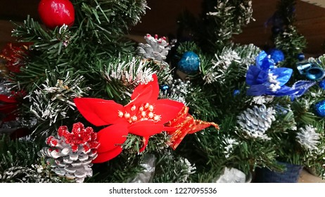 Holidays Background of Christmas Tree Branches decorated red berries, cons, and other decoration