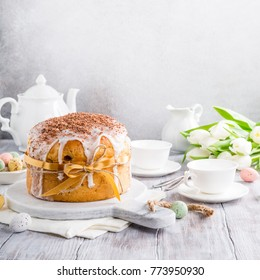 Holidays breakfast concept with copy space. Easter orthodox sweet bread, kulich and colorful quail eggs with white tulips. Copy space.