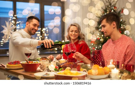 holidays and celebration concept - happy friends having christmas dinner at home and drinking red wine
