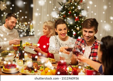 holidays and celebration concept - happy friends having christmas dinner at home, drinking red wine and clinking glasses over snow