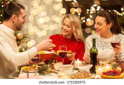 holidays and celebration concept - happy friends having christmas dinner at home, eating and drinking