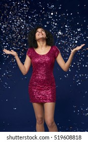 Holidays celebration concept. Happy young mixed race woman in fancy dress with sequins catching falling confetti at party