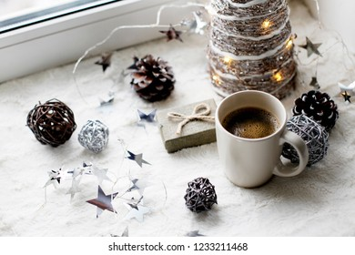 holidays, celebration and home concept - christmas tree, decoration and coffee cup against winter window. Holiday flat lay, hygge concept