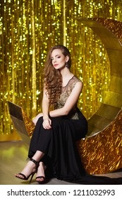 Holidays, celebration and people concept - young smiling woman in elegant dress over festive interior background