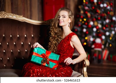 Holidays, celebration and people concept - young smiling woman in elegant red dress over christmas interior background