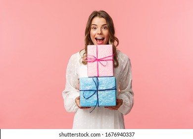 Holidays, celebration and women concept. Portrait of happy cheerful girl likes celebrating birthday and receive presents, holding two gift boxes and smiling camera, pink background