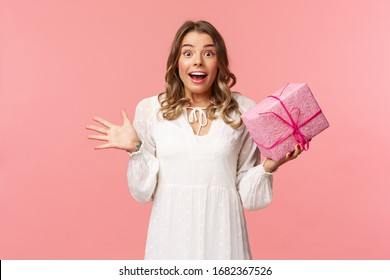 Holidays, celebration and women concept. Portrait of surprised upbeat charismatic blond girl in white dress, spread hands sideways and gasping amazed, receive surprise gift, hold pink box