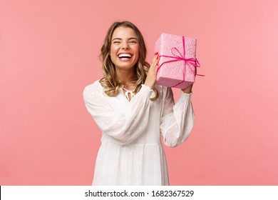 Holidays, celebration and women concept. Portrait of happy charismatic blond girl shaking gift box wondering whats inside as celebrating birthday, receive b-day presents, pink background
