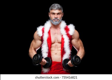 Holidays and celebrations, New year, Christmas, sports, bodybuilding, healthy lifestyle - Muscular handsome sexy Santa Claus. on a black background with dumbbells.