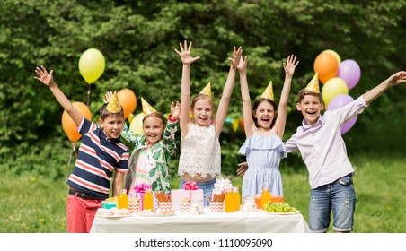holidays, childhood and celebration concept - happy kids hugging on birthday party at summer garden