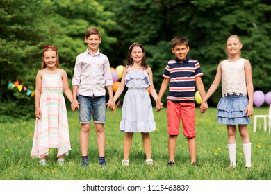 holidays, childhood and celebration concept - happy kids holding hands on birthday party at summer park