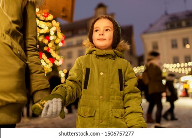 holidays, childhood and people concept - happy little boy with mother at christmas market in winter evening