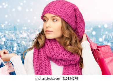 holidays, christmas, sale and people concept - young woman in winter clothes with shopping bags over snowy city background