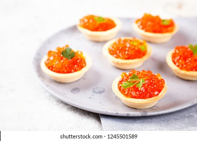 Holidays composition. Red Salmon Caviar in tartlet on a plate. Festive Appetizer  on  gray background.Copy space for Text.