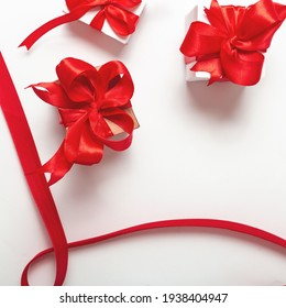 holidays concept. couple of packaged gifts with a red ribbon on a white background. Top view. Flat composition.