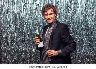 Holidays concept - happy tipsy man with bottle of champagne and wine glass at christmas or new year party on a sparkle background.