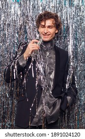 Holidays concept - happy tipsy man with a glass of champagne at christmas or new year party on a sparkle background.